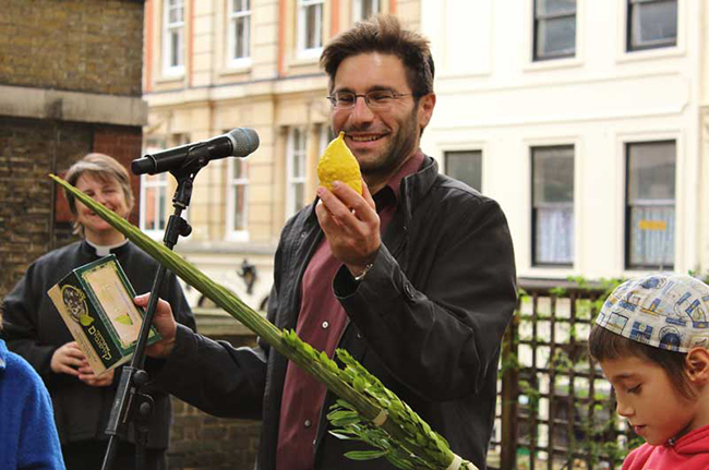 Rabbi Natan speaks at the Harvest/Sukkot celebration, with Rev Lucy Winkett to his right